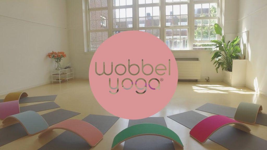 Erkend logo wobbel yoga met wobbel borden op de achtergrond