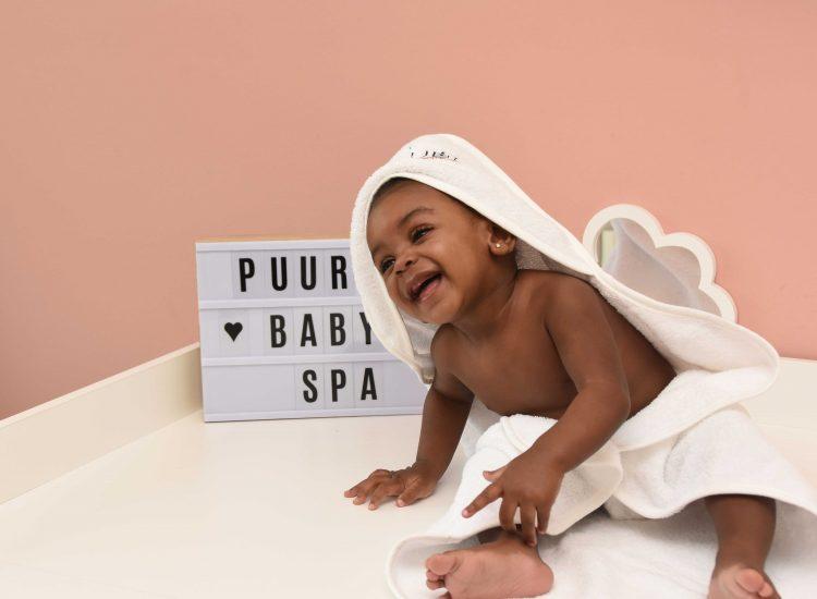 Lachende baby naast een lichtbox met de tekst Puur baby spa